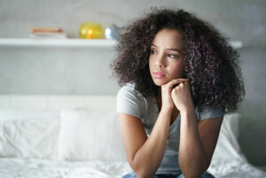 anxious Black woman sitting with hands together