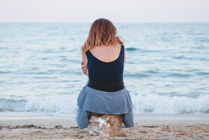 Grieving woman sitting at the beach
